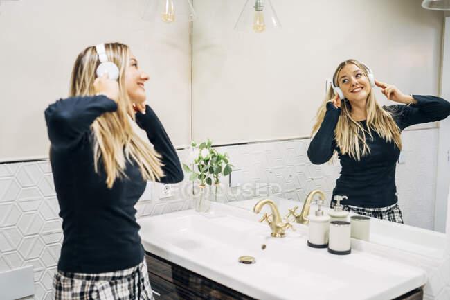Imagen de espejo de mujer feliz con auriculares bailando en el baño - foto de stock