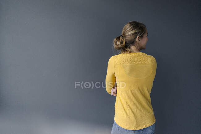 Rear view of young woman standing at a grey wall — Stock Photo