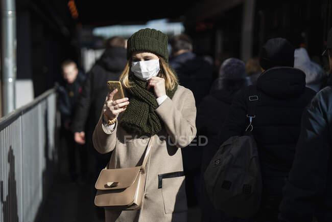 Mulher com máscara facial em pé na parada de ônibus, usando smartphone — Fotografia de Stock