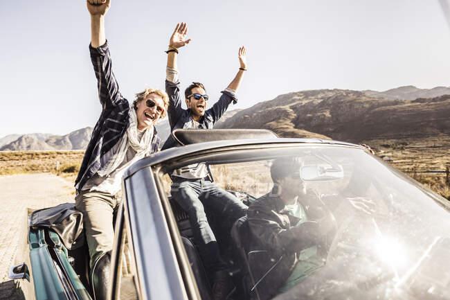 Счастливые друзья в конвертируемой машине во время путешествия — стоковое фото