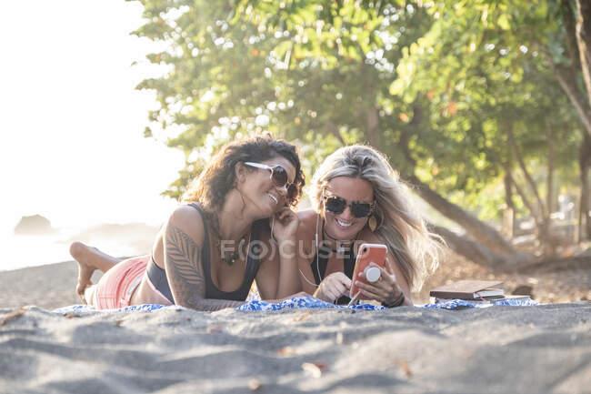 Dos mujeres felices escuchando música en la playa, Costa Rica - foto de stock