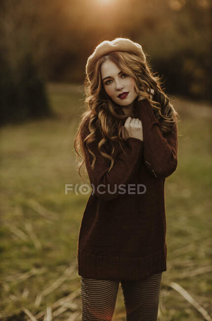 Portrait of fashionable woman standing on a meadow at backlight — Stock Photo