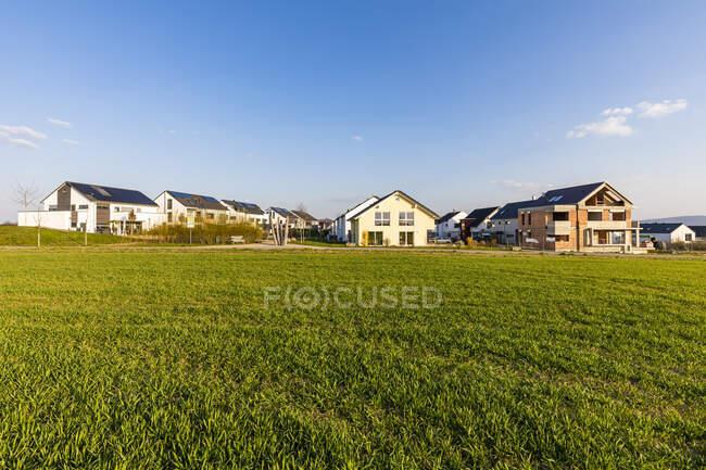 Alemanha, Baden-Wurttemberg, Waiblingen, Campo gramado na frente de modernas casas de subúrbios eficientes em termos energéticos — Fotografia de Stock