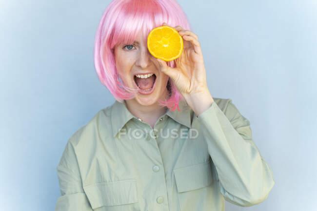 Retrato de una joven despreocupada con peluca rosa sosteniendo una naranja - foto de stock