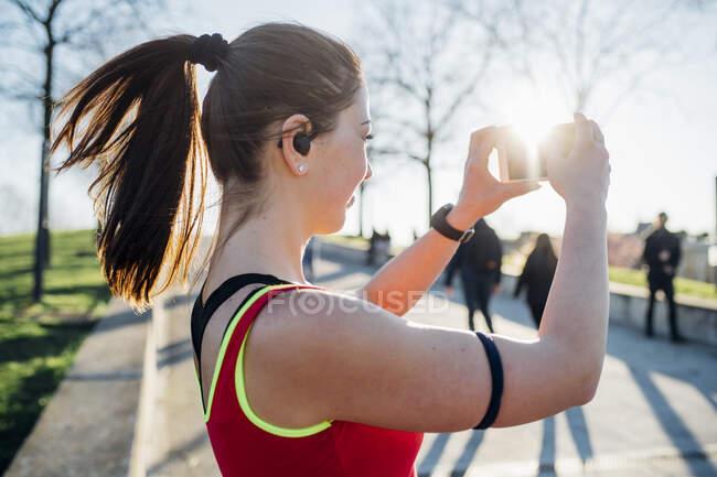 Спортивная молодая женщина с беспроводными наушниками делает селфи — стоковое фото