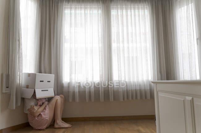 Donna che indossa una scatola di cartone sulla testa con sorriso annoiato e cowering sul pavimento — Foto stock