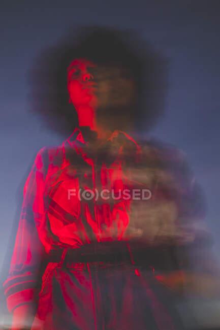 Mujer joven borrosa con peinado afro al aire libre por la noche - foto de stock