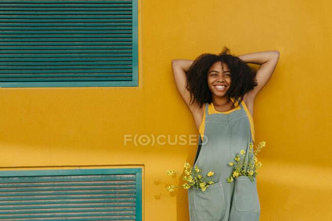 Портрет догляду за молодою жінкою, одягнена в комбінезон з квітами в кишенях. — стокове фото