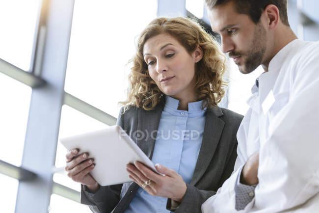 Безробітна жінка і лікар, які поділяють таблетку в лікарні. — стокове фото