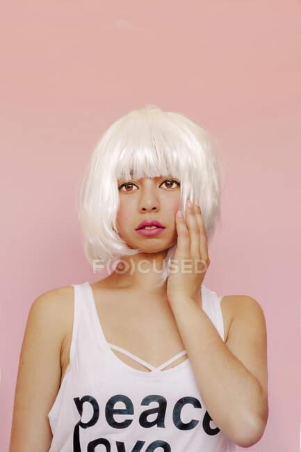 Портрет молодої жінки у білій перуці перед рожевим фоном. — стокове фото