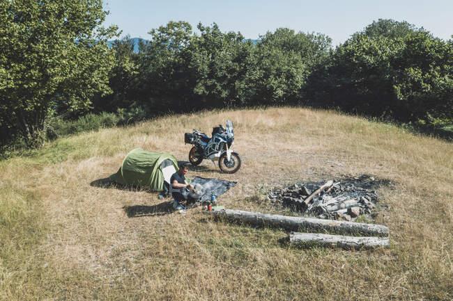 Hombre en un viaje en moto acampar en un prado remoto - foto de stock