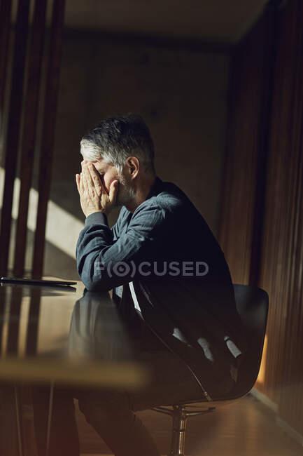 Hombre de negocios casual sentado en su oficina sostenible, cabeza en manos - foto de stock