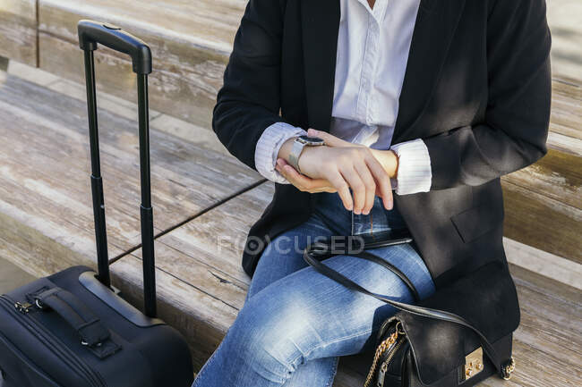 Вид на урожай молодой предпринимательницы с сумочкой и тележкой, сидящей на скамейке на открытом воздухе, проверяющей время — стоковое фото