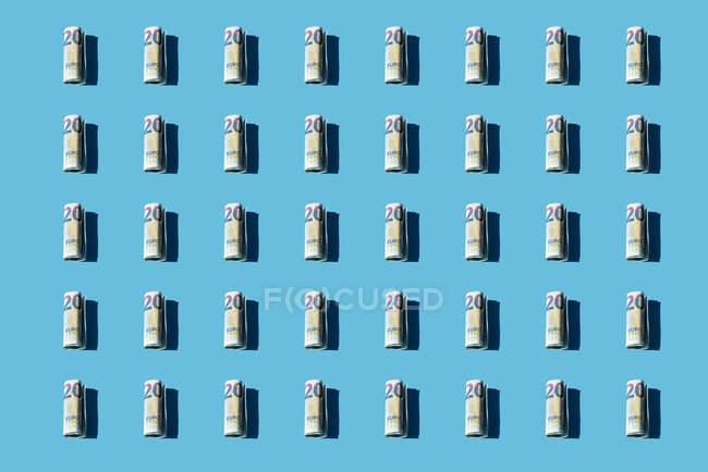 Modello di banconote da 20 euro arrotolate su sfondo blu — Foto stock