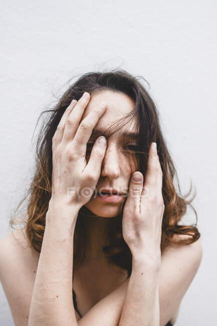 Retrato de una joven deprimida con las manos en la cara - foto de stock
