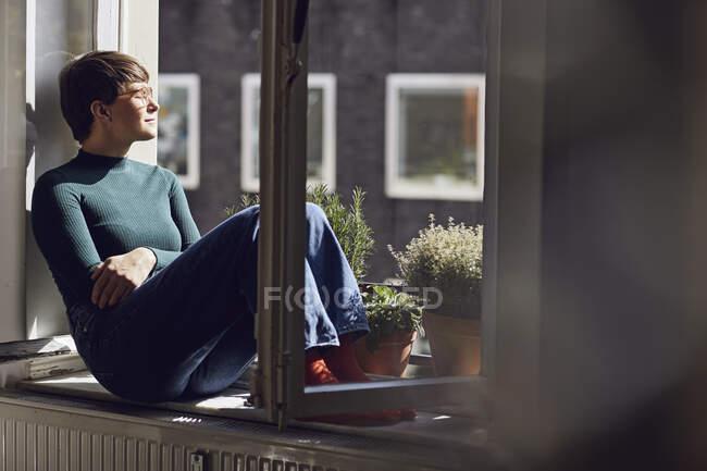 Mujer sentada en la ventana de casa - foto de stock