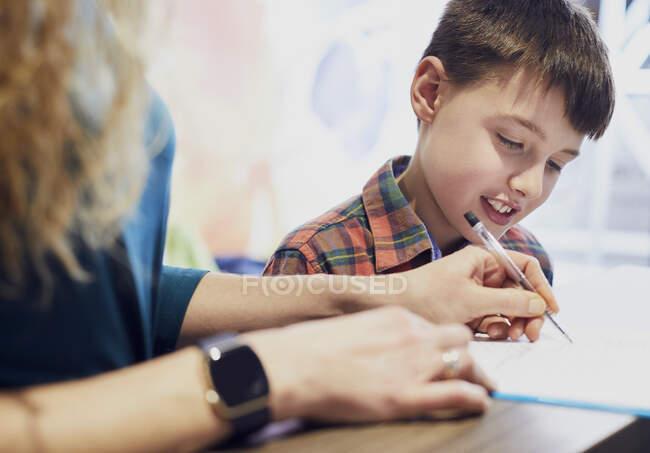 Madre llenando el formulario para su hijo en la consulta médica - foto de stock