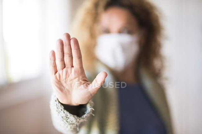 Mulher com máscara facial mostrando palma da mão, dizendo parar — Fotografia de Stock