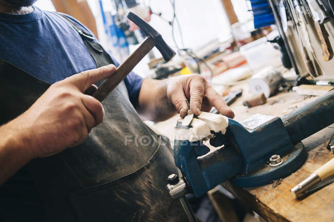 Craftsman working on knive in his workshop — Stock Photo