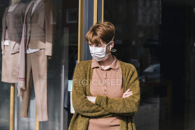 Donna che indossa maschera in piedi davanti al suo negozio di abbigliamento chiuso — Foto stock