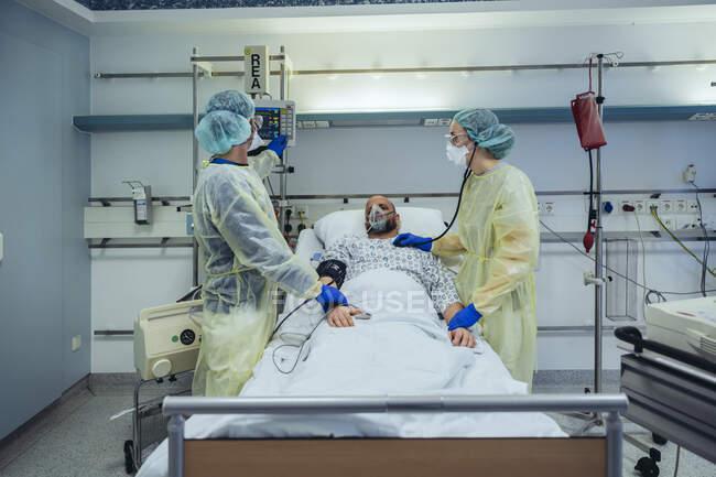 Médicos que cuidam do paciente em uma unidade de emergência de um hospital olhando para a tela — Fotografia de Stock