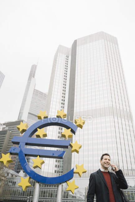 Uomo d'affari sorridente che parla sul cellulare mentre si trova contro la scultura e la Banca centrale europea, Francoforte, Germania — Foto stock