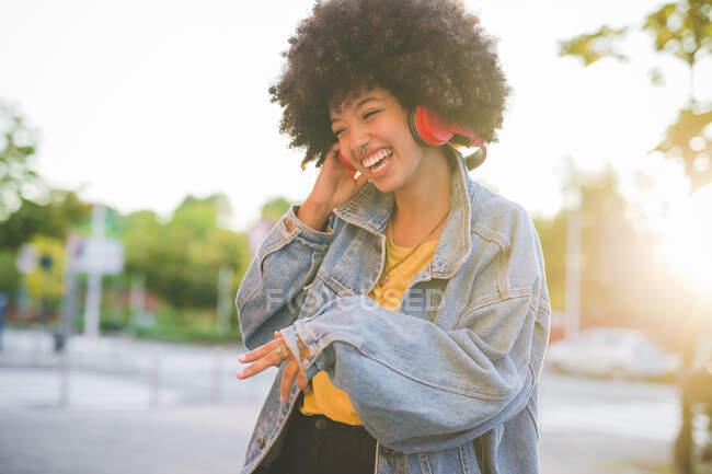 Jovencita feliz con peinado afro bailando en la ciudad - foto de stock