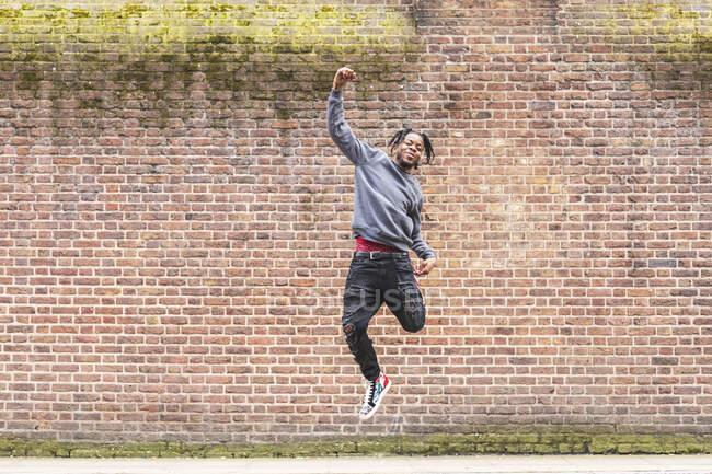 Junger Mann springt vor Ziegelmauer — Stockfoto
