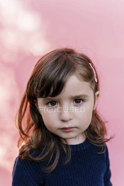 Портрет грустной маленькой девочки на розовом фоне — стоковое фото