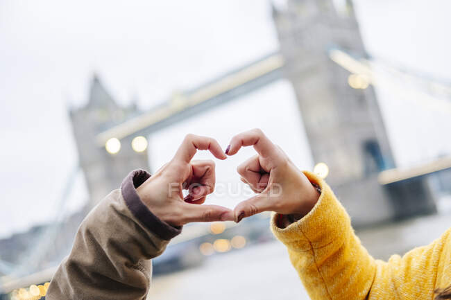 Hands making heart.shape with  London Bridge in background — Stock Photo