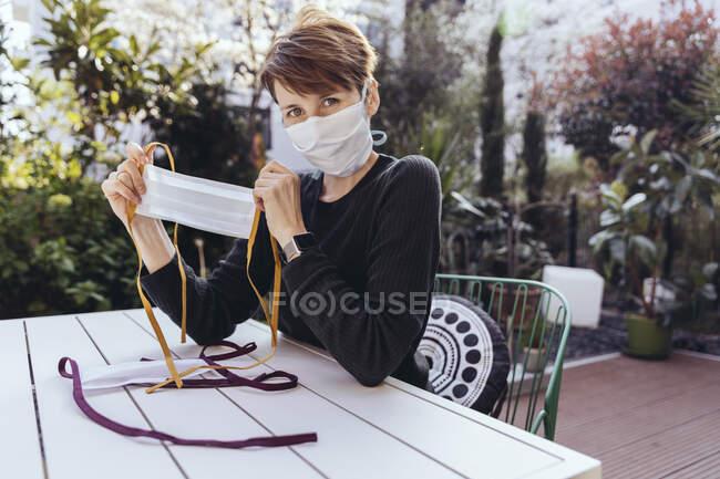 Mulher sentada no jardim, mostrando máscaras auto-feitas — Fotografia de Stock