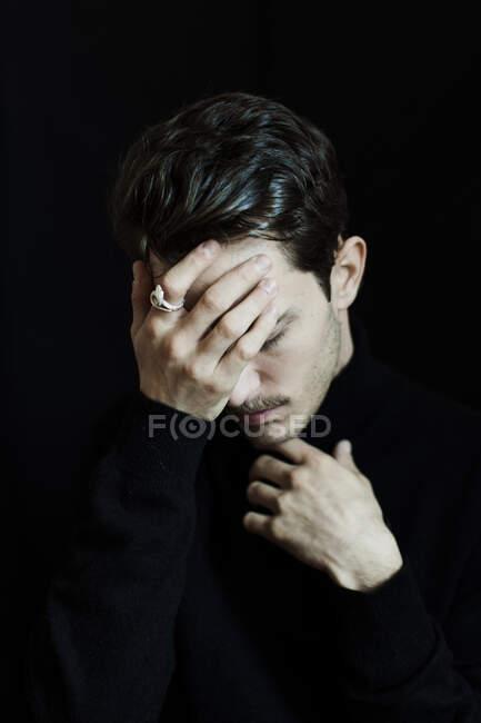 Портрет молодого чоловіка з закритими очима й закритими руками на чорному фоні. — стокове фото