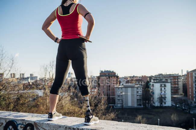 Jovem esportiva com prótese de perna em pé em uma parede acima da cidade, Milão, Itália — Fotografia de Stock