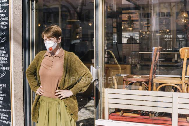 Mujer con máscara de pie frente a su restaurante cerrado - foto de stock