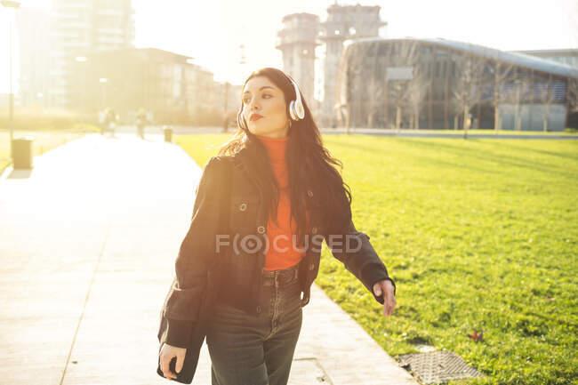 Женщина гуляет в парке и слушает музыку — стоковое фото