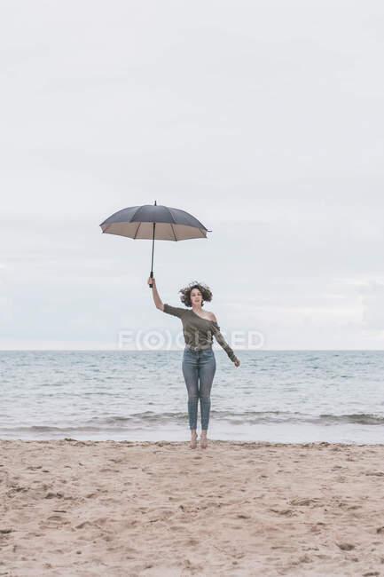 Mujer joven saltando en la playa, sosteniendo el paraguas — Stock Photo