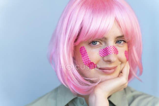Retrato de mujer joven con peluca rosa con yeso en la cara - foto de stock