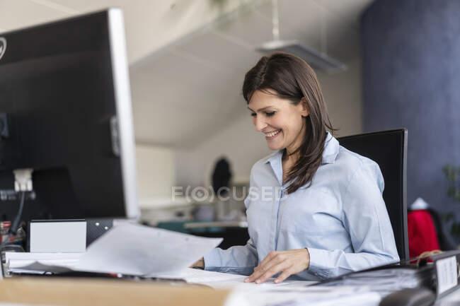 Усміхнена бізнес-жінка працює за столом в офісі. — стокове фото