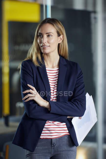 Посмішка ділова жінка тримає документи в офісі — стокове фото