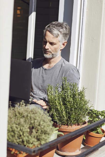 Hombre maduro sentado en la ventana en casa usando el ordenador portátil - foto de stock