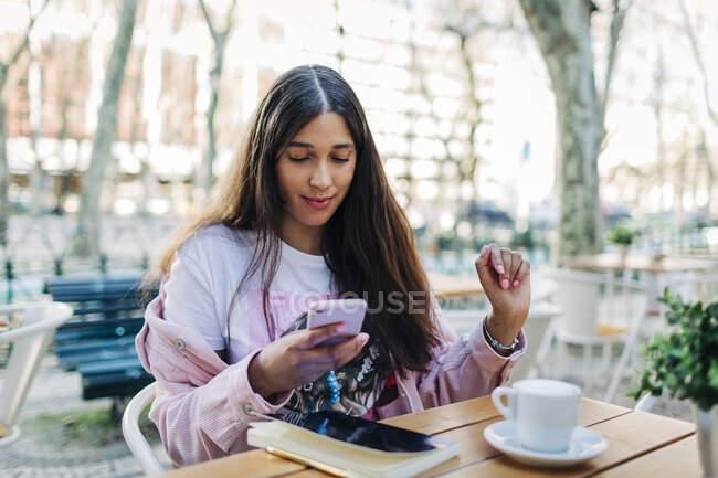 Mujer joven sentada en la mesa al aire libre y usando smartphone - foto de stock
