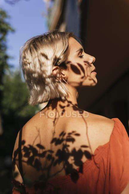 Профіль молодої жінки з тінями листя на обличчі і спині — стокове фото