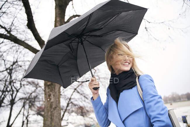 Sorrindo mulher loira segurando guarda-chuva na tempestade — Fotografia de Stock
