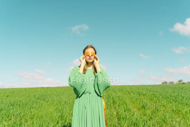Blindfolded young woman wearing a green dress standing in a field — стокове фото