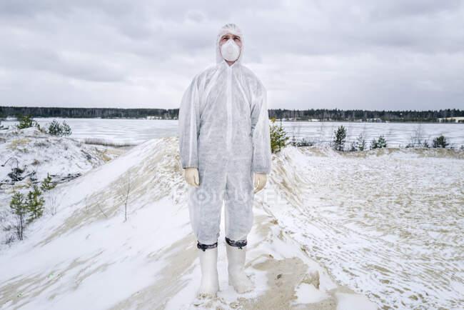 Чоловік у захисному костюмі й масці, що стоять у сільській місцевості взимку. — стокове фото