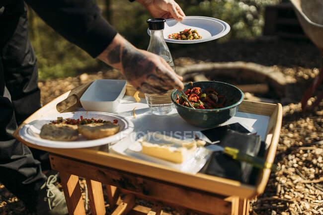 Gros plan de l'homme tatoué mettant le repas végétarien dans l'assiette dans le jardin — Photo de stock