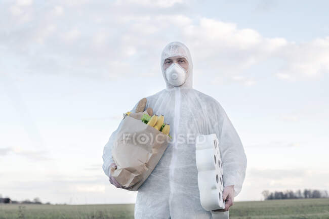 Homem vestindo roupa protetora e máscara segurando rolos de banheiro e saco de supermercado no campo — Fotografia de Stock