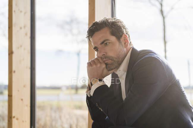 Un hombre de negocios serio sentado en la ventana de la oficina - foto de stock