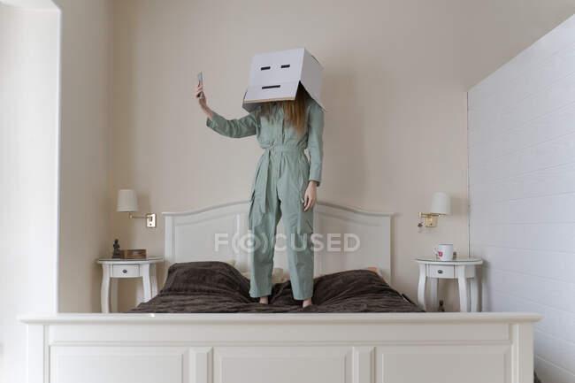 Mujer con una caja de cartón en la cabeza con sonrisa aburrida tomando una selfie en su cama - foto de stock