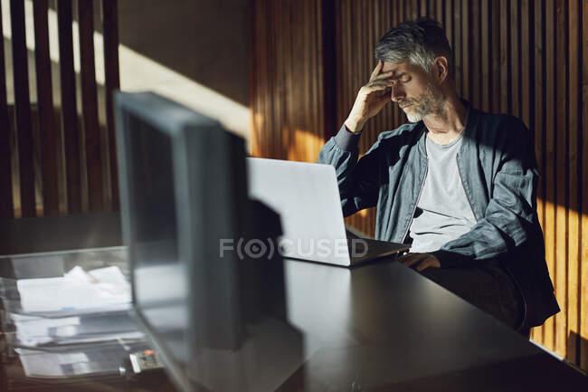 Hombre de negocios casual sentado en su oficina sostenible, tenía en la mano - foto de stock